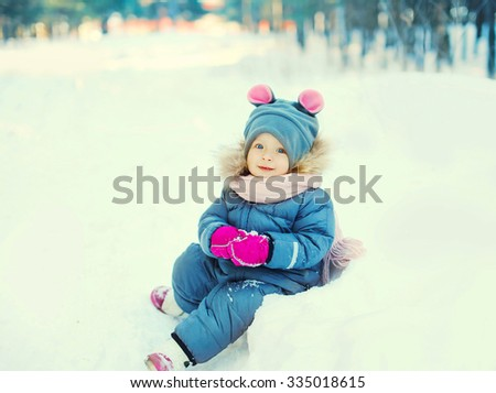 Happy little child sitting playing on snow in winter day - stock photo