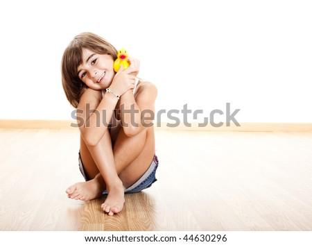 Happy little child smilling and playing with a yellow rubber duck - stock photo
