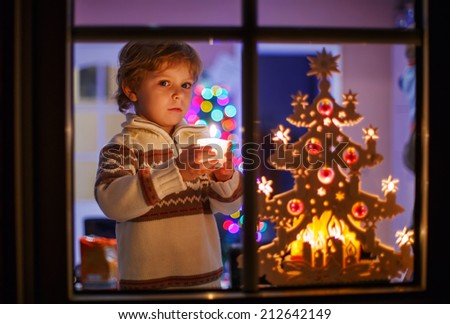 Happy little child standing by window at Christmas time and blowing candle. With colorful lights from Christmas tree on background, selective focus. - stock photo