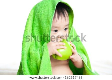 Happy little child wrapped in green towel, isolated over white eating fruit - stock photo