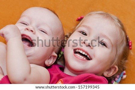 happy little children brother and sister hugging lying on an orange background - stock photo