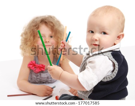 Happy little children drawing with pencils at home