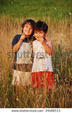 Happy little children in grass on meadow - stock photo
