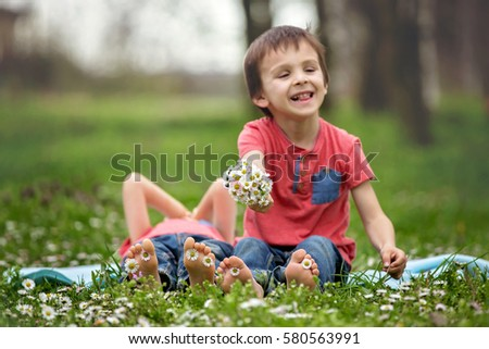 Happy little children, lying in the grass, barefoot, daisies around them, playing happily, childhood happiness concept
