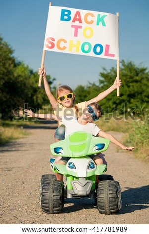 Happy little children playing on road at the day time. They driving on quad bike in the park. People having fun on the nature. Concept of the kids are ready to go to school. - stock photo
