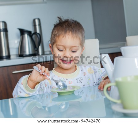 Happy little cute boy in pajamas eating breakfast at a table in the kitchen