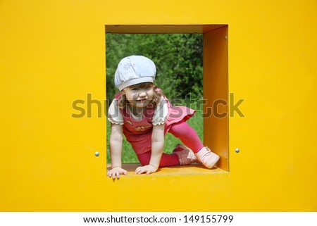 Happy little cute girl climbs in window of yellow box at playground at summer day.  - stock photo