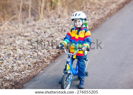 Happy little cyclist boy riding bike and having fun on cold  day, outdoors. Active leisure with children in winter, sping or autumn. - stock photo
