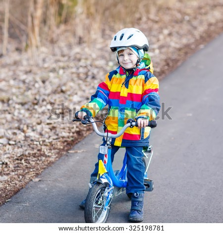 Happy little cyclist boy riding bike and having fun on cold  day, outdoors. Active leisure with children in winter, sping or autumn.