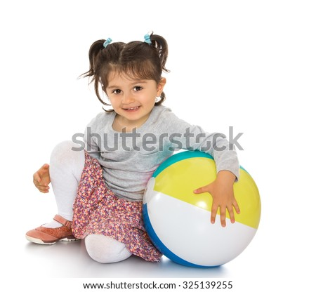 Happy little dark haired girl with small pigtails on her head sitting on the floor and holding the arm of a big inflatable striped ball. Isolated on white background - stock photo