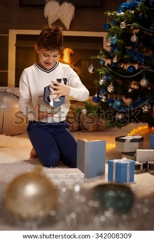 Happy little excited boy opening christmas present, smiling surprised. - stock photo