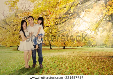 Happy little family standing under autumn tree enjoying holiday - stock photo