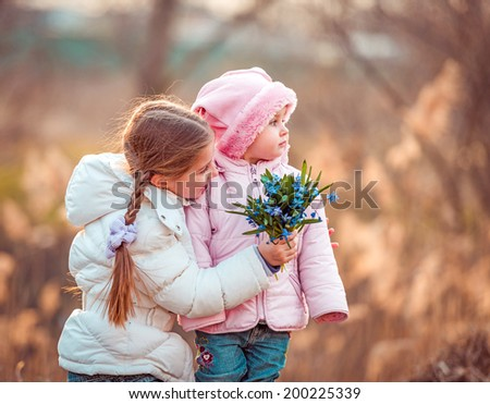 happy little girl and her sister holding a bouquet of flowers - stock photo