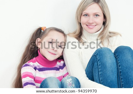 Happy little girl and her young mother sitting by each other on the floor