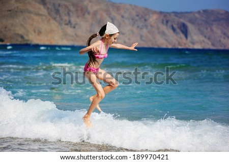 Happy little girl at beach during summer vacation jumping in waves - stock photo