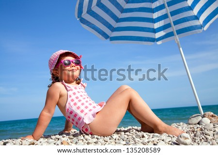 happy little girl at the seaside under an umbrella in the summer - stock photo