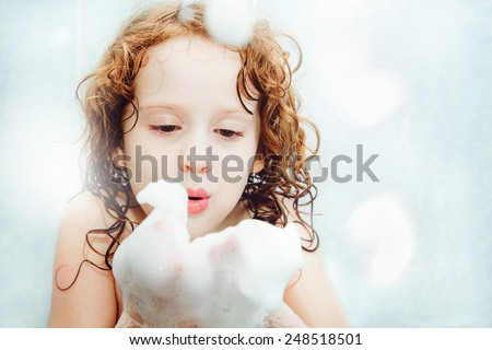 Happy little girl blowing foam with her hand. - stock photo