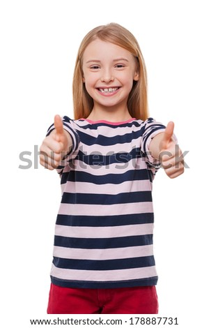 Happy little girl. Cheerful little girl showing her thumbs up while standing isolated on white - stock photo