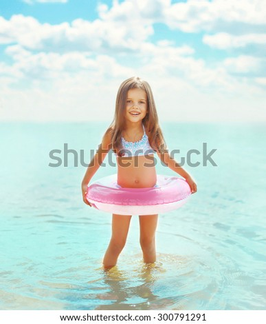 Happy little girl child bathing with inflatable circle and having fun in the sea  - stock photo
