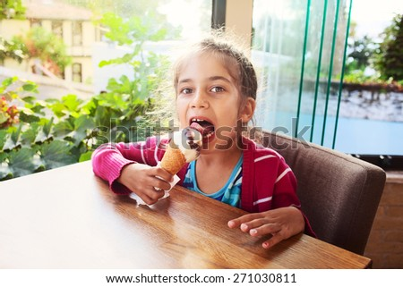 Happy little girl child kid chocolate eating ice cream in cafe near  open window - stock photo