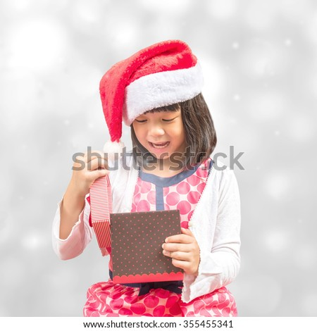 Happy little girl child kid with santa claus hat opening gift box with surprise on silver white shimmering light bokeh background on seasonal holiday occasions, Merry christmas and Happy new year 2016 - stock photo