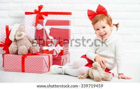 happy little girl child with Christmas gifts at a blank brick wall - stock photo