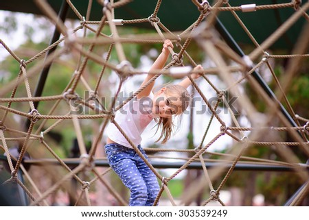 Happy little girl climbing on a rope playground outdoor - stock photo