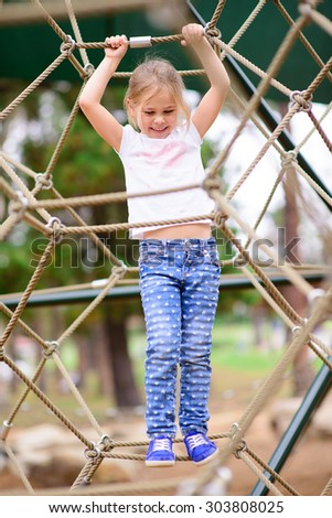 Happy little girl climbing on a rope playground outdoor