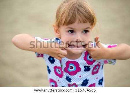 Happy little girl climbing on outdoor playground - stock photo