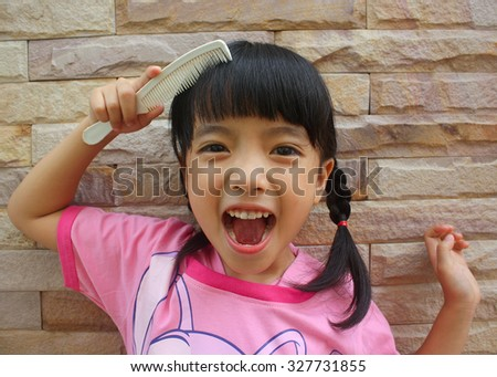 Happy little girl combing her hair at brick wall background, selective focus - stock photo