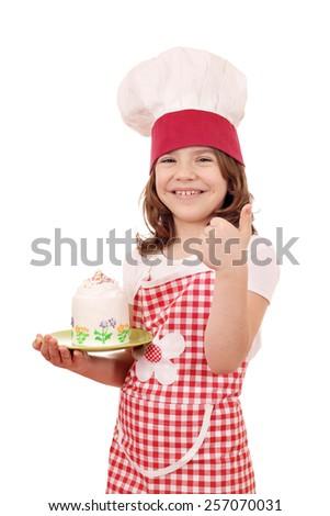 happy little girl cook with cake and thumb up - stock photo