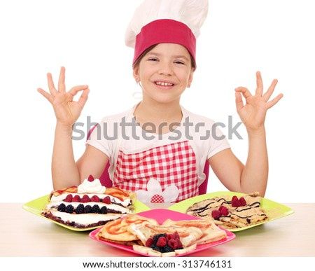 happy little girl cook with delicious crepes on table and ok hand sign - stock photo