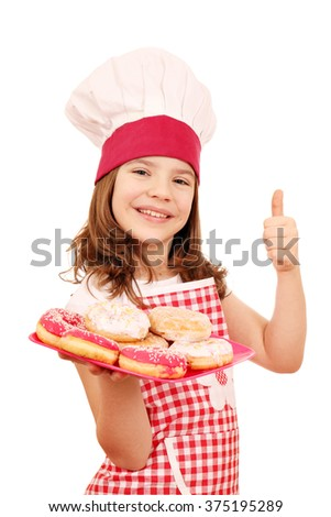 happy little girl cook with donuts and thumb up - stock photo