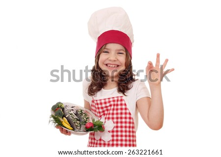 happy little girl cook with fish and ok hand sign - stock photo