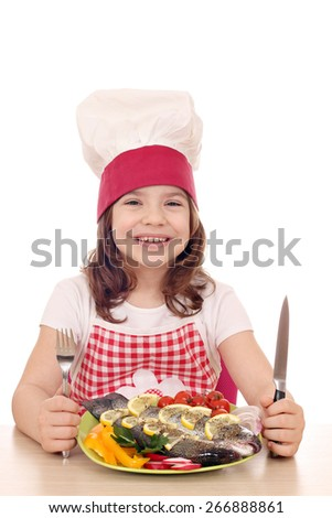 happy little girl cook with prepared fish ready for lunch - stock photo