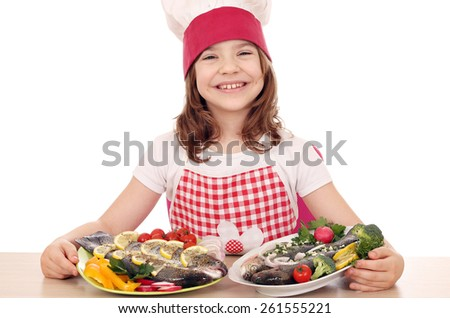 happy little girl cook with prepared fishes  - stock photo