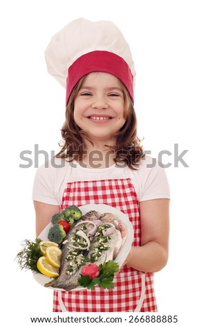 happy little girl cook with prepared trouts on plate - stock photo