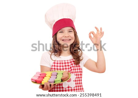 happy little girl cook with sweet macarons and ok hand sign - stock photo