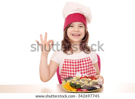 happy little girl cook with trout and ok hand sign - stock photo