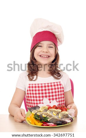 happy little girl cook with trout fish - stock photo