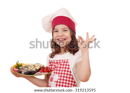happy little girl cook with trout fish and ok hand sign - stock photo