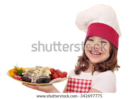 happy little girl cook with trout fish and salad on plate - stock photo