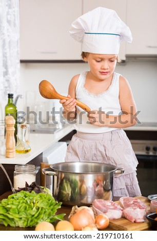 Happy little girl cooking with meat at home kitchen