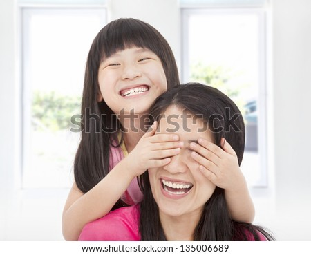 happy little girl cover her mother eyes for fun - stock photo