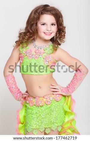 Happy little girl dancer latin, emotional gymnastic girl in carnival costume. Little ballerina girl in colorful dress isolated on white in studio. series - stock photo