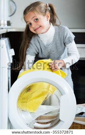 Happy little girl doing laundry in home interior - stock photo