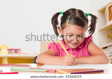 Happy little girl drawing with pencils at home - stock photo