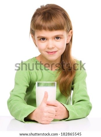 Happy little girl drinks milk, isolated over white - stock photo