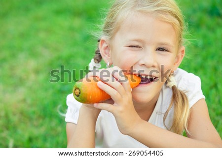 Happy little girl eating carrot at the day time. Concept of healthy food. - stock photo