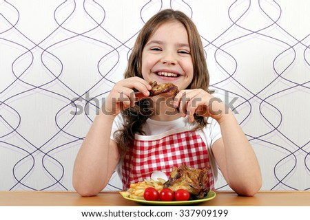 happy little girl eating chicken wings  - stock photo